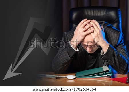 Disgruntled man next to a falling graph. He is holding his head. Businessman is upset about crisis. He is unhappy with financial depression. Businessman went bankrupt. Boss is upset with bankruptcy Royalty-Free Stock Photo #1902604564