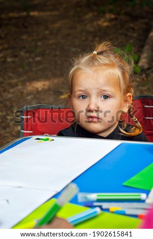 Children draw in nature. Lots of colored papers and pencils on a blue table. Girls play outdoors. Drawing lesson in the park. Sad girl at the table.