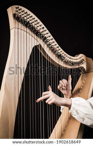 Hands playing wooden harp on black background Royalty-Free Stock Photo #1902618649