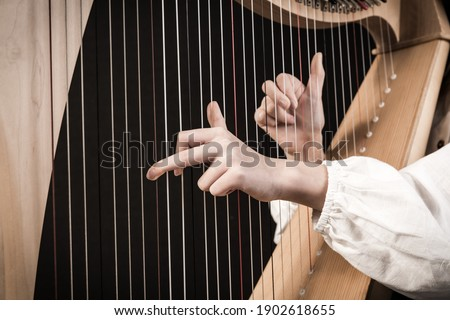 Hands playing wooden harp on black background Royalty-Free Stock Photo #1902618655