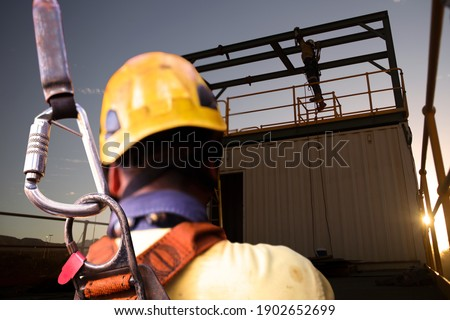 Safety workplace construction worker wearing yellow safety helmet fall arrest PPE harness attached an inertia reel shock absorber device on harness defocused workmate using standing working background Royalty-Free Stock Photo #1902652699