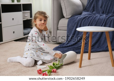 Emotional little girl and broken ceramic vase on floor at home Royalty-Free Stock Photo #1902658249
