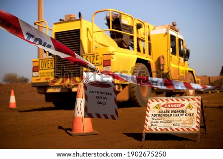 Safe workplace practice red and white warning danger tag tape sign applying taping off working area dropped object with crane lifting high risk work exclusion dropped zone construction site background Royalty-Free Stock Photo #1902675250