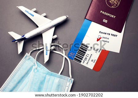 Traveling during COVID-19 pandemic, passport with airline ticket, covid-19 negative test, medical masks and plane on grey background, airport security health and safety check concept Royalty-Free Stock Photo #1902702202