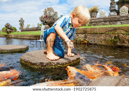 Happy kids walk with fun by pond stepping stones, feeding golden koi fishes in Tirta Gangga garden with natural water pools. Culture, arts of Bali, popular travel destination in Indonesia. Royalty-Free Stock Photo #1902725875