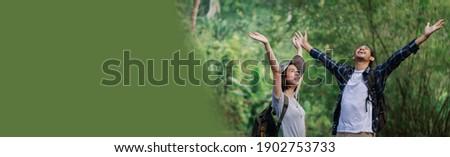 Banner or web header ratio image. Happy couple hiking outdoors in forest. Active young Caucasian woman hiker and Asian man.