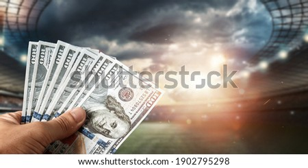 Close-up of a man's hand holding US dollars against the background of the stadium. The concept of sports betting, making a profit from betting, gambling. American football Royalty-Free Stock Photo #1902795298