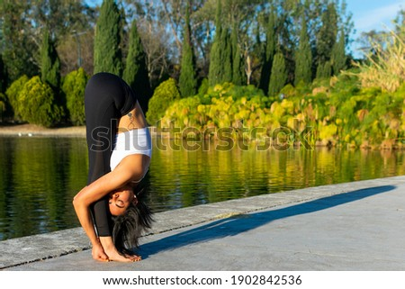 Young brunette attractive sporty girl practicing yoga, doing folding exercise, posed uttanasana, exercising, wearing sportswear and in a lake in the background. Concept of self-love Royalty-Free Stock Photo #1902842536