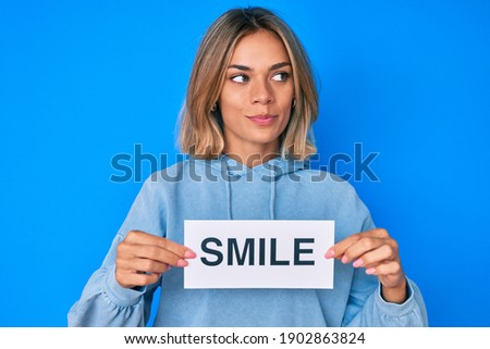 Beautiful caucasian woman holding smile text smiling looking to the side and staring away thinking.  Royalty-Free Stock Photo #1902863824