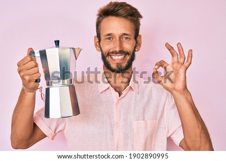 Handsome caucasian man with beard holding italian coffee maker doing ok sign with fingers, smiling friendly gesturing excellent symbol