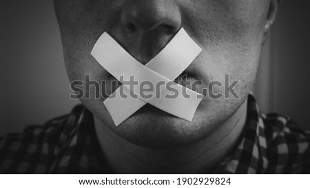A man with an adhesive plaster sealed his mouth, a man with a closed mouth with adhesive tape, a man cannot open his mouth. Closed mouth Royalty-Free Stock Photo #1902929824