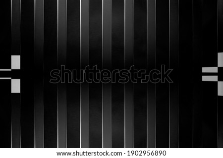 Close-up photo of black vertical blinds on window. Striped pattern. Abstract geometric background image of interior design, modern architecture, industry or technology. Stripes and parallel lines. Royalty-Free Stock Photo #1902956890