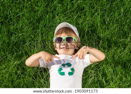 Happy child points fingers at recycle sign on t-shirt. Funny kid against spring green background. Ecology and Earth day concept. Top view Royalty-Free Stock Photo #1903091173