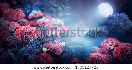 Fantasy magical enchanted fairy tale landscape with forest lake, fabulous fairytale blooming pink rose flower garden and two butterflies on mysterious blue background and glowing moon ray in night Royalty-Free Stock Photo #1903127728