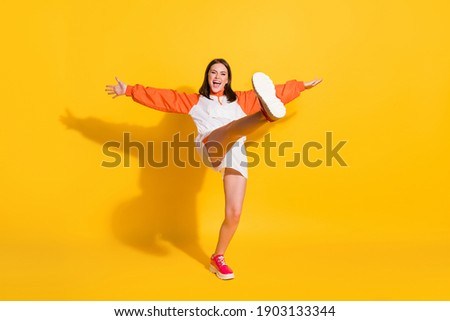 Full length photo portrait of girl standing on one leg kicking isolated on vivid yellow colored background Royalty-Free Stock Photo #1903133344