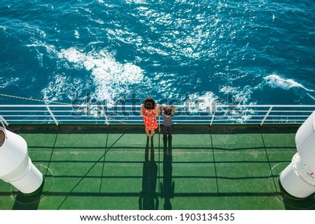 The family is sailing on a cruise ship, a mother with  son are standing at the fence on the ship and looking at the sea, traveling by ferry, a boy with mom are sailing on a ship. Royalty-Free Stock Photo #1903134535