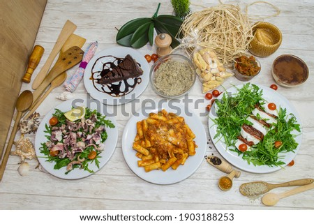 Composition of several Italian dishes, special Italian ingredients and preparations. Picture in top view with culinary decoration in background.