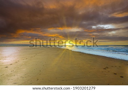 Deserted beach during sunset with orange deep blue colored clouds and low sun with sun rays on the horizon shining over the beach Royalty-Free Stock Photo #1903201279