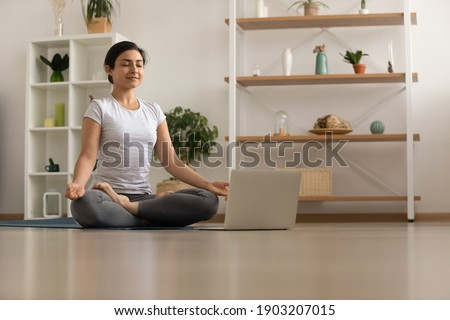 Serene millennial mixed race woman engaged in yoga practice breath deep feel comfort harmony. Tranquil inspired young indian lady sit by laptop on floor at lotus asana meditate to reach peace of mind Royalty-Free Stock Photo #1903207015