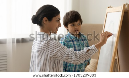 Attentive little indian boy preschooler take painting class from young millennial woman art teacher. Interested small child son watch inspired mother drawing picture on white board with colored chalks