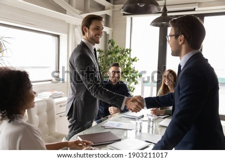 Happy business partners shaking hands at corporate meeting, standing in boardroom, making successful deal, agreement, signing contract, smiling executive team leader greeting new worker at briefing