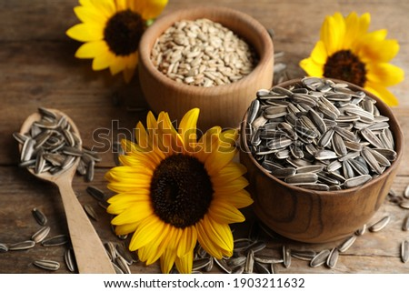 Organic sunflower seeds and flowers on wooden table Royalty-Free Stock Photo #1903211632