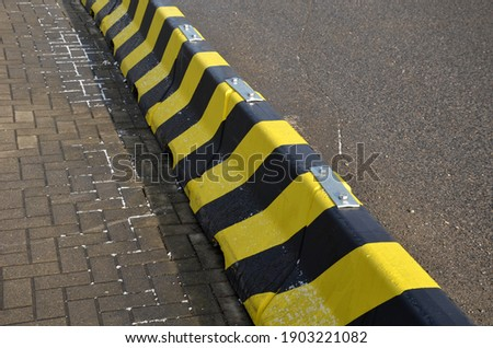 horizontal stripes for traffic signs. highway concrete barriers on the road. vehicle lane separator. yellow color with black stripes. protects pedestrians in a dangerous turn Royalty-Free Stock Photo #1903221082