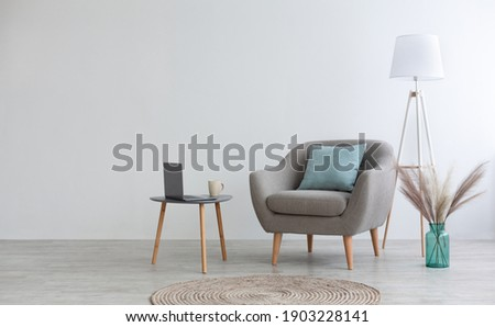 Cozy boho design for remote work and leisure at home. Gray vintage armchair with pillow, table with cup of coffee and laptop, vase with dry plants, lamp and carpet on floor, on light wall background Royalty-Free Stock Photo #1903228141