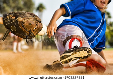 Cropped photo of softball player sliding into home plate Royalty-Free Stock Photo #1903229851