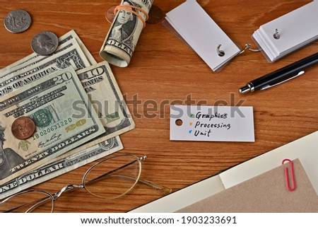 There is a word book with the word Graphics Processing Unit which is a financial term written on it. It is on a desk with bills, glasses and notebook.