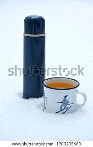 Hot white enamelled cup of orange tea with picture of skier in the snow with blue thermos next to it. Winter refreshment. Cold weather.
