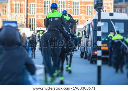 """Dutch police squad formation and horseback riding mounted police back view with """"Police"""" logo emblem on uniform maintain public order after football game and rally in the streets of Amsterdam center Royalty-Free Stock Photo #1903308571"""
