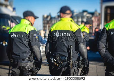 """Dutch police squad formation and horseback riding mounted police back view with """"Police"""" logo emblem on uniform maintain public order after football game and rally in the streets of Amsterdam center Royalty-Free Stock Photo #1903308592"""