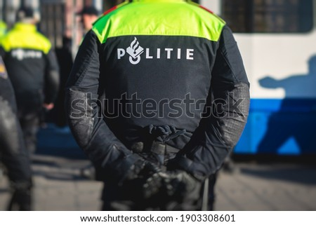 """Dutch police squad formation and horseback riding mounted police back view with """"Police"""" logo emblem on uniform maintain public order after football game and rally in the streets of Amsterdam center Royalty-Free Stock Photo #1903308601"""