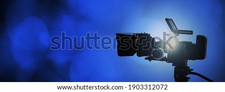 Professional video camera on dark blue abstract background, broadcast or movie production banner with copy space Royalty-Free Stock Photo #1903312072