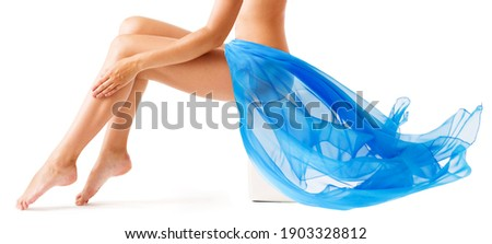Beauty Woman Legs Skin. Leg Wax Depilation. Body Care. Flying Blue Fabric Wave. Isolated White Royalty-Free Stock Photo #1903328812