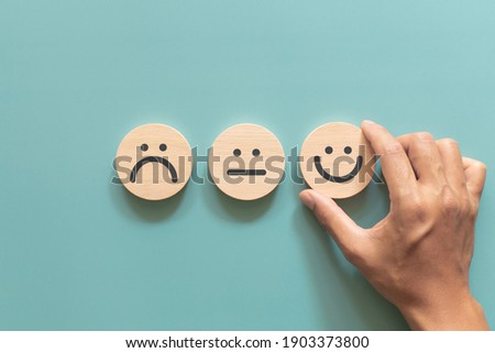 Customer putting wood sphere smile face emoticon for rating. Service rating, feedback, satisfaction concept Royalty-Free Stock Photo #1903373800