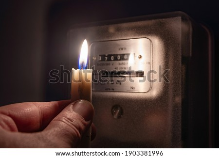 A man's hand with candle in complete darkness looking on electricity meter at home. Power outage, blackout concept.  Royalty-Free Stock Photo #1903381996