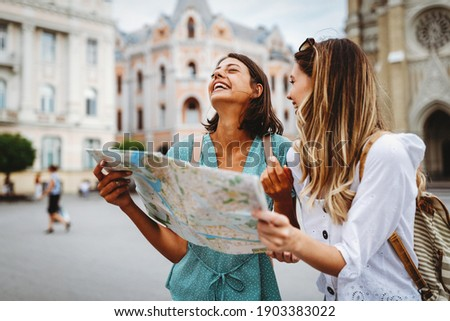 Fun, friends, travel and tourism concept. Beautiful girls looking for direction in the city Royalty-Free Stock Photo #1903383022