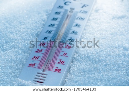 The thermometer lies on the snow in winter showing a negative temperature. Meteorological conditions in a harsh climate in winter with low air and ambient temperatures.Freeze in wintertime Royalty-Free Stock Photo #1903464133
