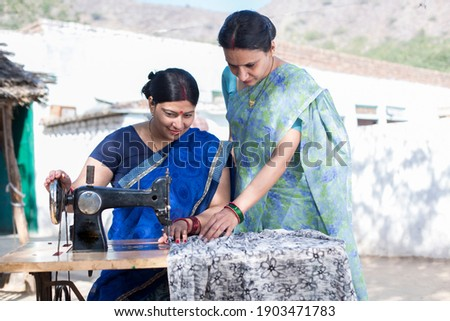 Happy Indian woman sewing clothes with sewing machine Royalty-Free Stock Photo #1903471783