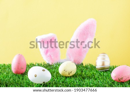 Easter bunny ears and Easter eggs on grass over yellow background. Easter greeting card.