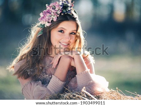 Beautiful young woman with white teeth and a perfect smile. Happy sincere outdoor portrait of an attractive model with flowers