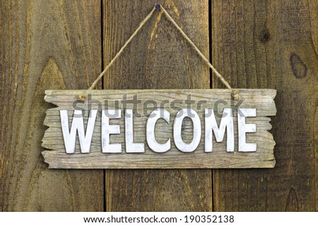 Welcome sign hanging by rope on rustic antique wood door; aged wooden  background