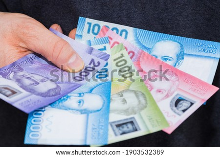 Chilean Banknotes, Different Values, Money spread out and held in the hand Royalty-Free Stock Photo #1903532389