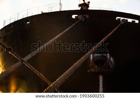 Stretched mooring lines from the cargo ship. Moored cargo ship. Royalty-Free Stock Photo #1903600255