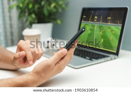 Close up cropped shot of male hand holding smartphone. Man watching soccer play live broadcast online on his laptop and making bets on his favourite team using mobile application. Royalty-Free Stock Photo #1903610854
