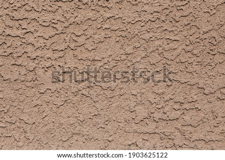 A tan colored abstract stucco background. Royalty-Free Stock Photo #1903625122