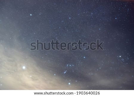 The brightest star Sirius near the constellation Orion in the foggy night.