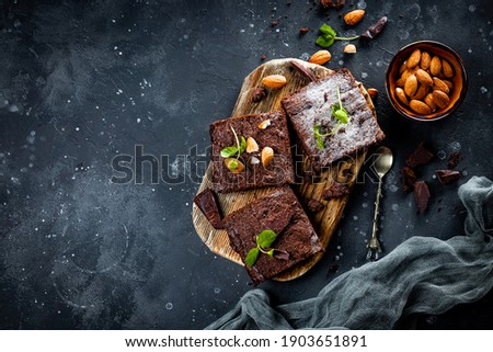 Pieces of homemade chocolate brownie with mint leaves and nuts on the gray background, top view copyspace